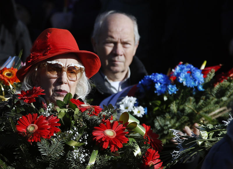 A woman holds flowers during the funeral of Kosovo Serb politician Oliver Ivanovic, in Belgrade, Serbia, Thursday, Jan. 18, 2018. Ivanovic was gunned down Tuesday morning in the northern Kosovo city of Mitrovica. (AP Photo/Darko Vojinovic)