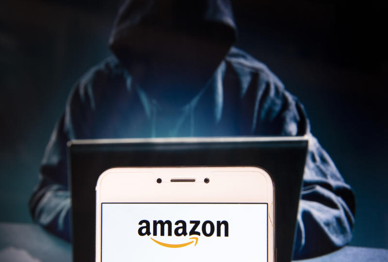 HONG KONG - 2018/11/22: In this photo illustration, the American electronic commerce and cloud computing company Amazon logo is seen displayed on an Android mobile device with a figure of hacker in the background. (Photo Illustration by Miguel Candela/SOPA Images/LightRocket via Getty Images)