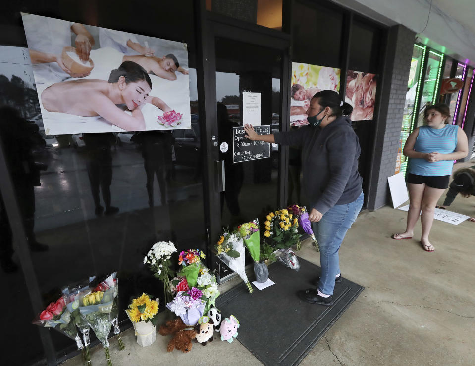 FILE - In this March 17, 2021, file photo, Jessica Lang pauses and places her hand on the door in a moment of grief after dropping off flowers with her daughter Summer at Youngs Asian Massage parlor where four people were killed in Acworth, Ga. While the U.S. has seen mass killings in recent years where police said gunmen had racist or misogynist motivations, advocates and scholars say the shootings this week at three Atlanta-area massage parlors targeted a group of people marginalized in more ways than one, in a crime that stitches together stigmas about race, gender, migrant work and sex work. (Curtis Compton/Atlanta Journal-Constitution via AP, File)