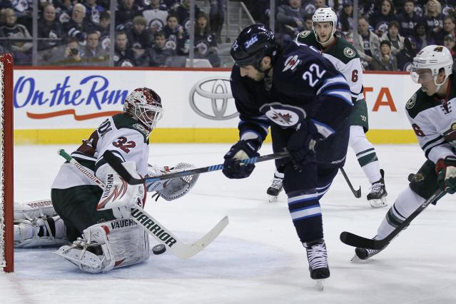 Minnesota Wild's goaltender Niklas Backstrom (32) gets a stick on Winnipeg Jets' Chris Thorburn's (22) shot as Wild's Marco Scandella (6) and Jared Spurgeon (46) look on during second-period NHL hockey game action in Winnipeg, Manitoba, Friday, Dec. 27, 2013. (AP Photo/The Canadian Press, John Woods)
