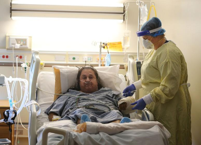 Memorial Hospital nurse Angela Bilyeu flushes the IV of patient Pedro Cortez in a COVID-19 unit on Friday, July 24, 2020. Medical facilities in Kern County are being pushed to the limit as more and more people contract COVID-19.