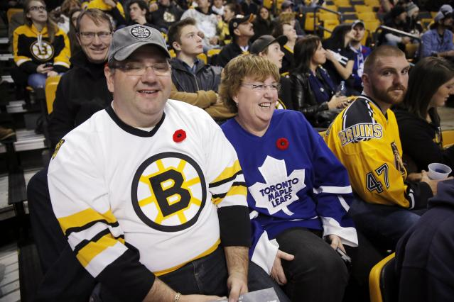 Tracy MacKenzie, left, and his wife Kim, from Nova Scotia, wait for the start of an NHL hockey game between the Boston Bruins and the Toronto Maple Leafs in Boston, Saturday, Nov. 9, 2013. (AP Photo/Michael Dwyer)