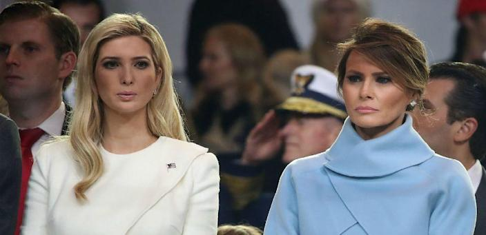 First lady Melania Trump (R), stands with Ivanka Trump as a parade passes the inaugural parade reviewing stand in front of the White House.