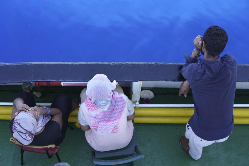 Migrants stand on the deck of the Open Arms Spanish humanitarian boat off the coast of the Sicilian island of Lampedusa, southern Italy, Sunday, Aug.18, 2019. An Open Arms spokeswoman tells The Associated Press that the humanitarian group is not willing to sail to Spain's southernmost Algeciras port given the emergency situation that they are experiencing inside the boat. (AP Photo/Francisco Gentico)