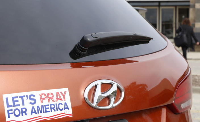 """With a """"Let's Pray For America"""" bumper sticker in the foreground, on Thursday, Oct. 25, 2018, a woman walks into a mall in Bloomingdale, Ill. that's housing a polling place for early voters. As Americans head to the polls for this midterm election, they are very polarized by issues from immigration and Supreme Court nominees to gun control. (AP Photo/Martha Irvine)"""