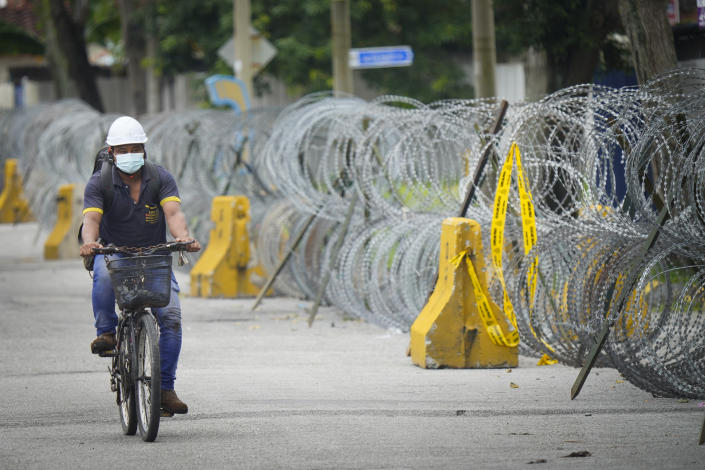 A men cycling next to coils of barbed wire near Top Glove factory hostel in Shah Alam, Malaysia, Wednesday, Nov. 25, 2020. Malaysia's Top Glove Corp., the world's largest maker of rubber gloves, says it expects a two to four-week delay in deliveries after more than 2,000 workers at its factories were infected by the coronavirus, raising the possibility of supply disruptions during the pandemic. (AP Photo/Vincent Thian)