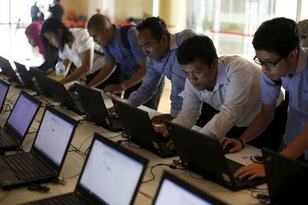 Indonesian youths fill up job application forms on laptops provided by organizers at the Indonesia Techno Career in Jakarta, June 11, 2015. REUTERS/Beawiharta