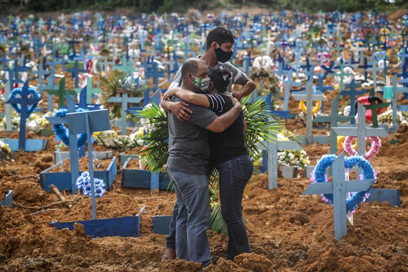 Relatives of a deceased person wearing protective masks mourn during a mass burial of coronavirus victims at the Parque Taruma cemetery on May 19, 2020, in Manaus, Brazil. / Credit: Andre Coelho / Getty Images