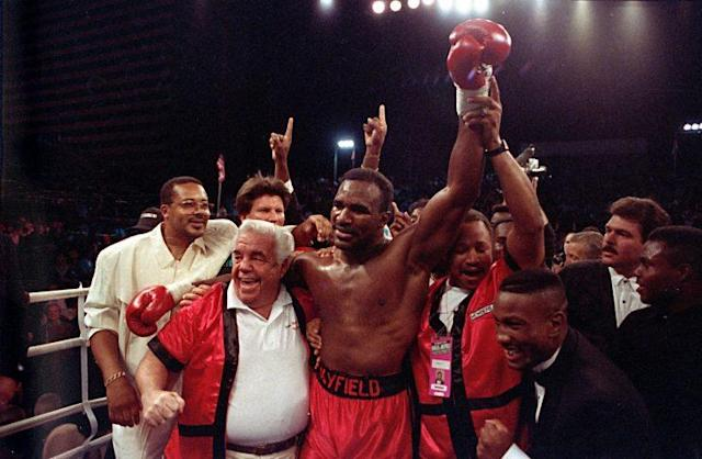 Lou Duva (L) celebrates with Evander Holyfield in Las Vegas after Holyfield knocked out Buster Douglas in 1990 to capture the heavyweight title. (The Associated Press)