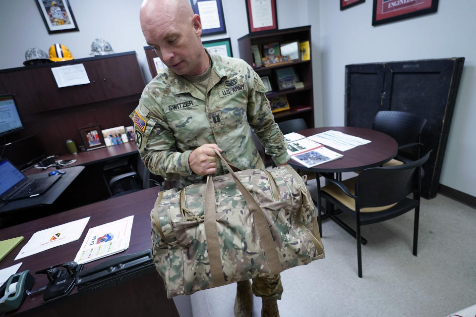 Capt. Michael Switzer goes to change into his sleepwear before going to sleep in his office at Camp Beauregard in Pineville, La., Friday, July 30, 2021. (AP Photo/Gerald Herbert)