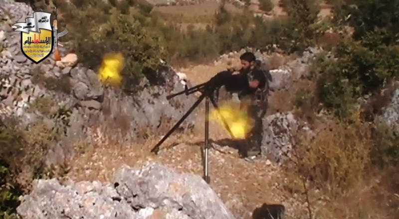 In this image taken from Sunday, Aug. 11, 2013, video obtained from the Sham News Network, which has been authenticated based on its contents and other AP reporting, a rebel fighter fires a gun in a valley in an unidentified location in Latakia province, Syria. Rebel military chief Gen. Salim Idris, the military commander of Syria's main Western-backed opposition group, visited rebels in the coastal province that is President Bashar Assad's ancestral homeland following recent opposition advances in the area, a spokeswoman said Monday. (AP Photo/Sham News Network via AP video)