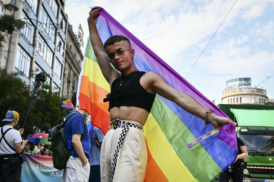 A participant poses with a rainbow flag during a gay pride parade in Budapest, Hungary, Saturday, July 24, 2021. Rising anger over policies of Hungary's right-wing government filled the streets of the country's capital on Saturday as thousands of LGBT activists and supporters marched in the city's Pride parade. (AP Photo/Anna Szilagyi)