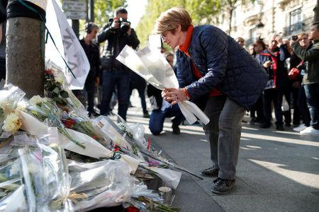 A woman leaves flowers on the Champs Elysees Avenue the day after a policeman was killed and two others were wounded in a shooting incident in Paris
