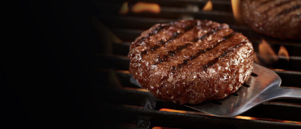 Image of a grilled Beyond Meat patty on a spatula coming off a grill.