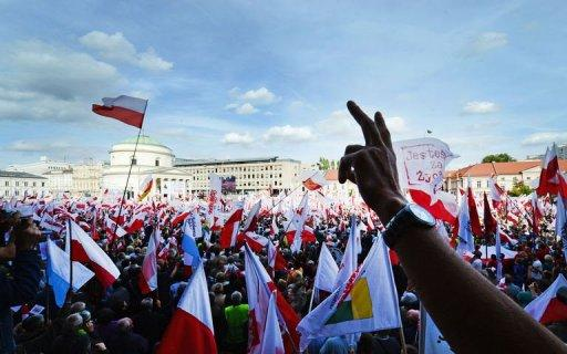 Demonstrators hold Polish national flags during an opposition rally