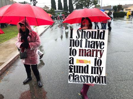 Los Angeles teachers carry signs as they picket in the rain in Los Angeles, California, U.S. January 16, 2018. REUTERS/Dan Whitcomb