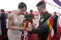 Lesbian couple Yumi Meng, left, puts a ring on Yi Wang' s finger during a military mass weddings ceremony in Taoyuan city, northern Taiwan, Friday, Oct. 30, 2020. Two lesbian couples tied the knot in a mass ceremony held by Taiwan's military on Friday in a historic step for the island. Taiwan is the only place in Asia to have legalized gay marriage, passing legislation in this regard in May 2019. (AP Photo/Chiang Ying-ying)