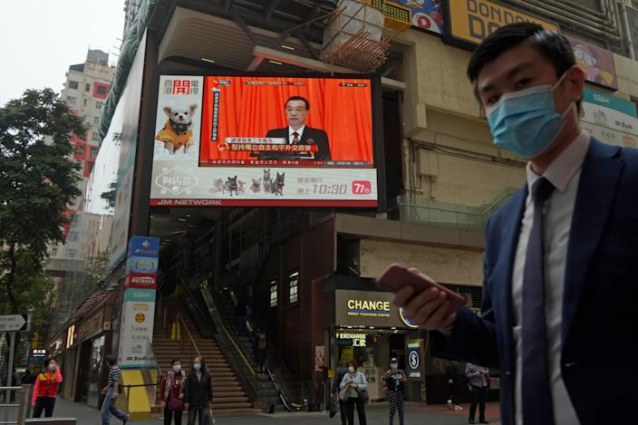 <p>A TV screen broadcasts the news of the opening session of China's National People's Congress (NPC) in Hong Kong on 5 March, 2021</p> (AP)
