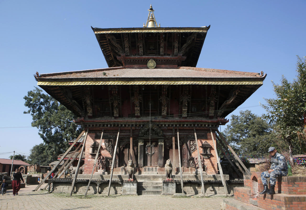 <p> In this Nov. 22, 2016 photo, a Nepalese policeman rests in front of Changu Narayan, a temple dedicated to Lord Vishnu, at Changu Village, 20 kilometers (12.5 miles) east of Kathmandu, Nepal. Less than two years after a 7.8 magnitude earthquake damaged the 5th century temple, the community is cleaning up their World Heritage site themselves and British architect John Sanday, who led the World Monuments Fund restoration of Cambodia's Angkor Wat, has taken on the recovery as his pet project. Changu Narayan is believed to be the oldest Hindu place of worship in the country, its wooden walls intricately carved with hundreds of deities, perched atop a steep hill overlooking the Kathmandu Valley. (AP Photo/Niranjan Shrestha) </p>