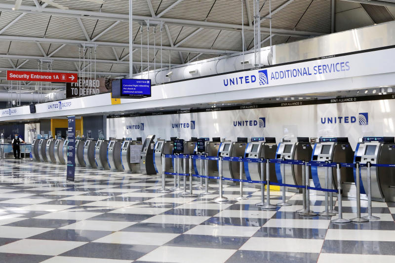 FILE - In this June 25, 2020, file photo, rows of United Airlines check-in counters at O'Hare International Airport in Chicago are unoccupied amid the coronavirus pandemic. On Sunday, Aug. 30, 2020, United Airlines says it will be dropping an unpopular $200 fee for most people who change a ticket for travel within the United States. (AP Photo/Teresa Crawford, File)