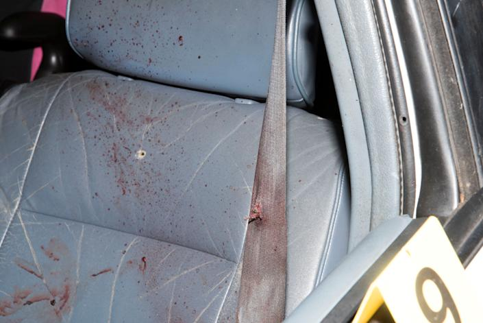 Bloodstains and bullet holes are seen in the front seat.