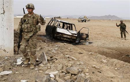 A U.S. soldier stands at the site of a suicide attack on a NATO base in Zhari