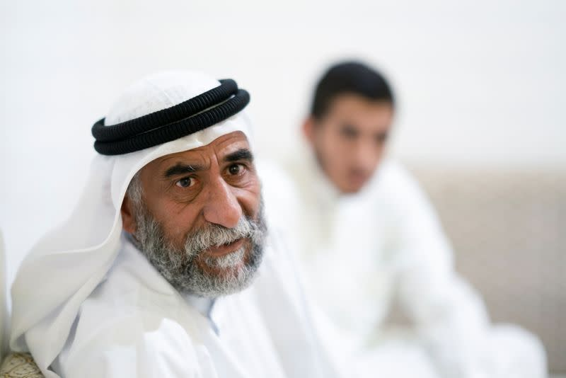 Abu Ahmad al-Enezi, a stateless sits with his son at their home in Sulaibiya