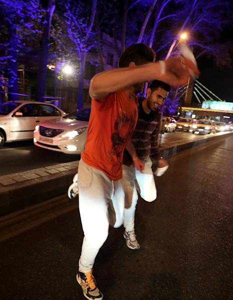 Men dance as they celebrate on Valiasr street in northern Tehran on April 2, 2015, after the announcement of an agreement on Iran nuclear talks (AFP Photo/Atta Kenare)