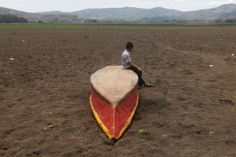 In a photo from May 2017, a boy sits on an abandoned boat on what is left of Guatemala's Lake Atescatempa, which dried up due to drought and high temperatures. (Photo: MARVIN RECINOS via Getty Images)