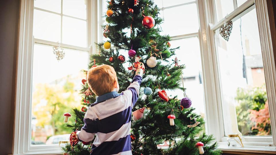 A young red head boy is decorating the Christmas tree in his home.