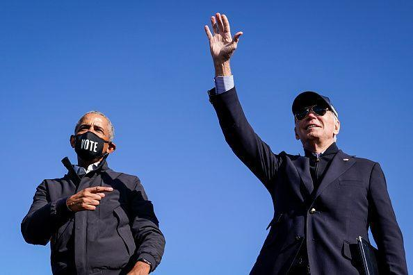 <p>Obama and Biden wave to the crowd at the end of a drive-in campaign rally at Northwestern High School on October 31, 2020 in Flint, Michigan. The state, which went to Trump in 2016, flipped back to Biden in the 2020 election, a key victory for the former VP in the race. </p>
