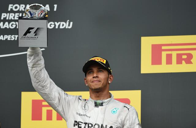 Mercedes' British driver Lewis Hamilton celebrates on the podium after the Hungarian Formula One Grand Prix at the Hungaroring circuit in Budapest on July 27, 2014 (AFP Photo/Dimitar Dilkoff)