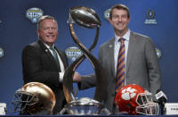 Notre Dame head coach Brian Kelly, left, and Clemson head coach Dabo Swinney share a moment during the NCAA Cotton Bowl football coaches' news conference in Dallas, Friday, Dec. 28, 2018. Notre Dame is scheduled to play Clemson in the NCAA Cotton Bowl semi-final playoff Saturday. (AP Photo/LM Otero)