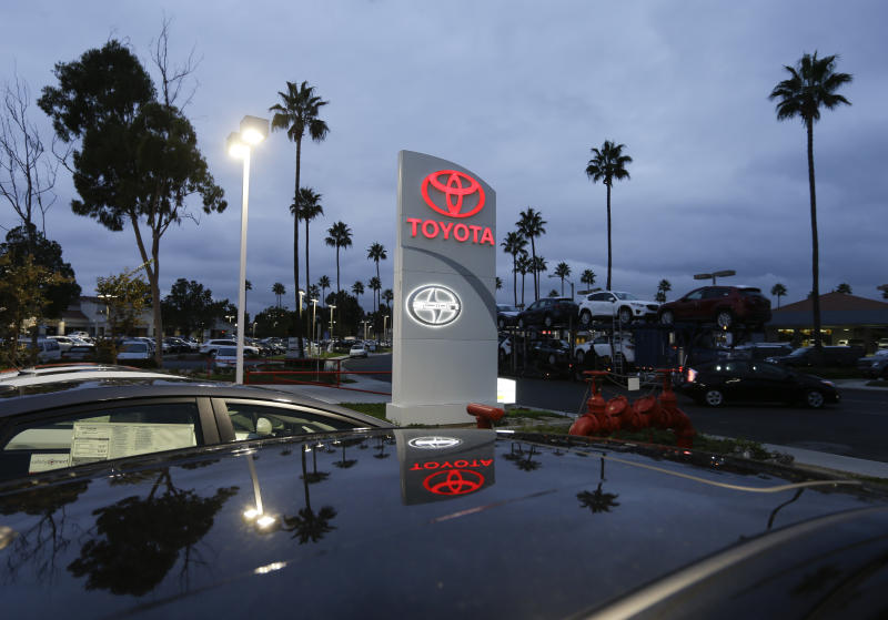 In this Thursday, Nov. 8, 2012, photo, a Toyota dealership signs glows over a car lot in Tustin Calif., Thursday, Nov. 8, 2012. A better economy and extra demand after Superstorm Sandy lifted U.S. auto sales in November. (AP Photo/Chris Carlson)