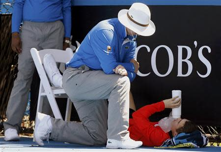 An official attends to a ball boy who collapsed during the men's singles match between Daniel Gimeno-Traver of Spain and Milos Raonic of Canada at the Australian Open 2014 tennis tournament in Melbourne January 14, 2014. REUTERS/Brandon Malone