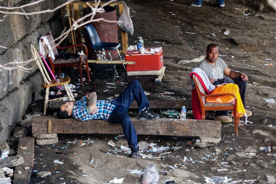 """A man is passed out next to another man after they both injected themselves with heroin along the Conrail line in Philadelphia's West Kensington neighborhood, also known as the """"Badlands."""""""