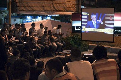 Egyptians watch presidential hopeful former Arab League General Secretary Amr Mussa speaking during a television live debate at a public screening in Cairo. Egypt held its first ever debate between presidential candidates on Thursday, as the two frontrunners for this month's election traded political accusations on television