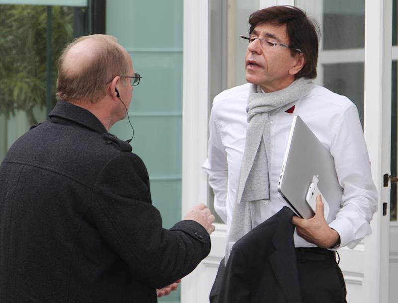 Belgium's Prime Minister Elio Di Rupo, right, talks with a plain clothes police officer ahead of an emergency meeting to discuss the closure of an ArcelorMittal plant in Liege, Belgium, in Brussels, Friday, Jan. 25, 2012. The world's leading steel and mining company ArcelorMittal announced Thursday it will close a coke plant and six production lines in Belgium, in a move that threatens 1,300 jobs. (AP Photo/Yves Logghe)