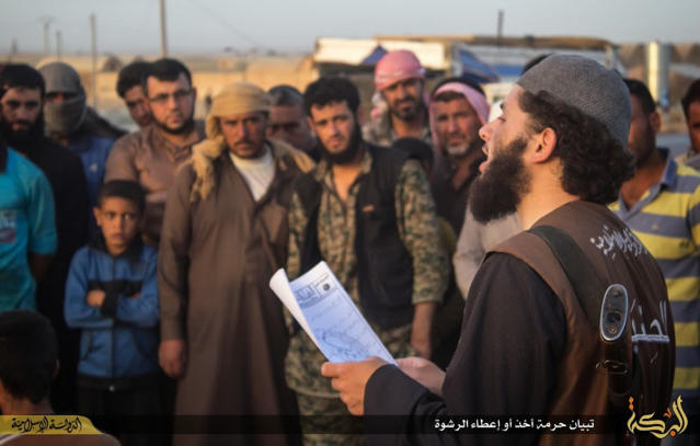 In this file photo released on May 14, 2015, by a militant website, which has been verified and is consistent with other AP reporting, a member of the Islamic State group's vice police known as Hisba, right, reads out to Syrian citizens, background, a verdict handed down by an Islamic court sentencing many they accused of adultery to lashing, in Raqqa city, Syria. (Militant website via AP, File)