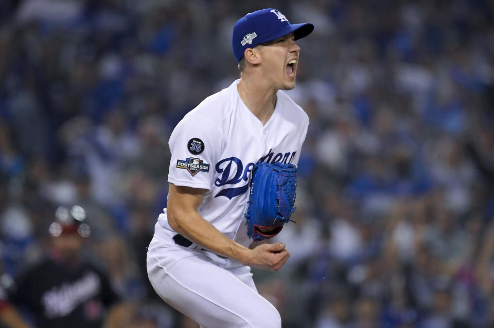 FILE - In this Oct. 9, 2019 file photo, Los Angeles Dodgers starting pitcher Walker Buehler celebrates after striking out Washington Nationals' Ryan Zimmerman to end the top of the sixth inning in Game 5 of a baseball National League Division Series in Los Angeles. In what's become a familiar refrain, the Dodgers arrive at camp still looking for their first World Series championship since 1988. After losing in two straight World Series, they were ousted by Washington in five games in the NL Division Series last fall. (AP Photo/Mark J. Terrill, File)