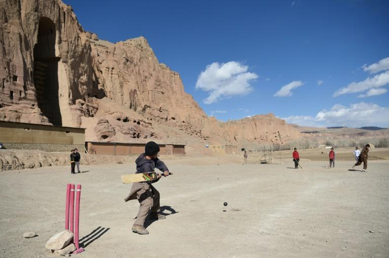 Youths play cricket near the site of the Bamiyan Buddha statues, which were destroyed by the Taliban in 2001
