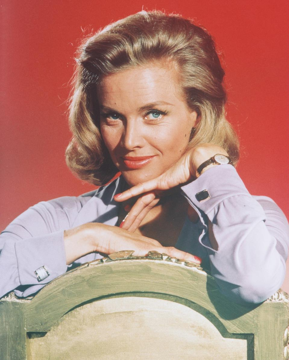 Honor Blackman, British actress, posing in a studio portrait, aginst a red background, issued as publicity for the film, 'Goldfinger', circa 1964. The James Bond film, directed by Guy Mailton, starred Blackman as 'Pussy Galore'. (Photo by Silver Screen Collection/Getty Images)