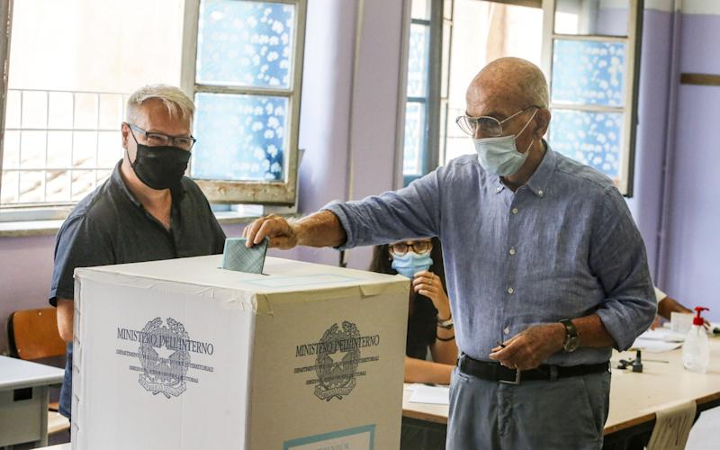 A voter wearing a protective face mask casts his ballot for the constitutional referendum on the reduction of lawmakers - Anadolu