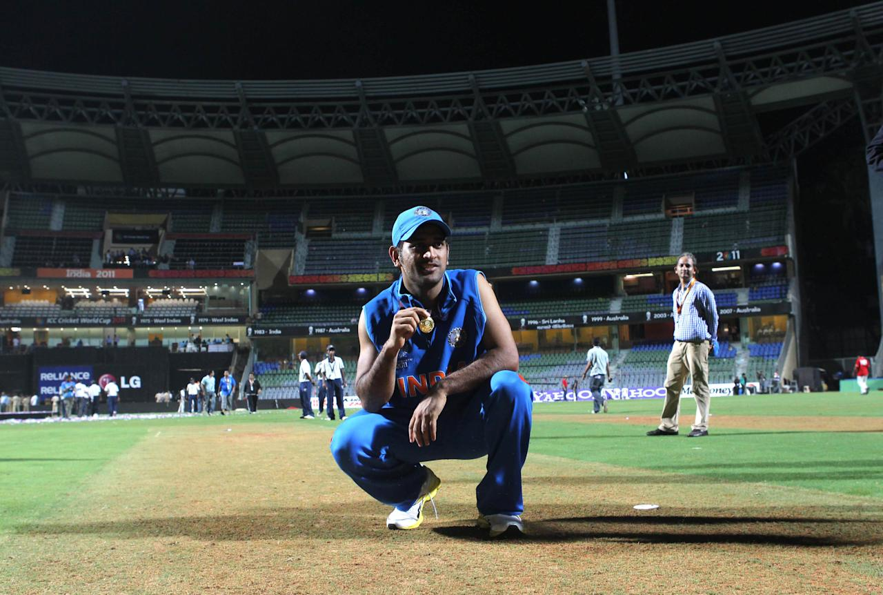 MUMBAI, INDIA - APRIL 2:  Indian captain Mahendra Singh Dhoni poses on the wicket after India won the final of 2011 ICC World Cup beating Sri Lanka by 6 wickets at Wankhede stadium in Mumbai, India on April 2, 2011. (Photo by Santosh Harhare/Hindustan Times via Getty Images)