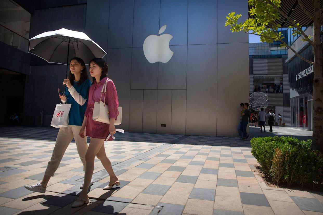 People walk past an Apple store at a shopping mall in Beijing, Saturday, June 29, 2019.