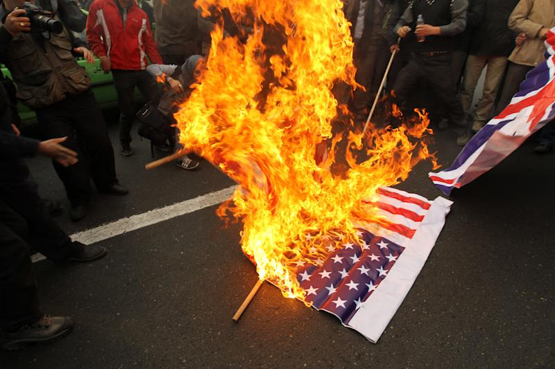 Iranian demonstrators, mainly members of the hardline Islamist Basij militia, burn British and US flags during a demonstration outside Britain's embassy in downtown Tehran on December 12, 2010 over the killing of a top Iranian nuclear scientist last month. Iranian leaders have pointed an accusing finger at the British intelligence service the MI6 as well as US and Israeli intelligence over the assassination. AFP PHOTO/ATTA KENARE (Photo credit should read ATTA KENARE/AFP via Getty Images)