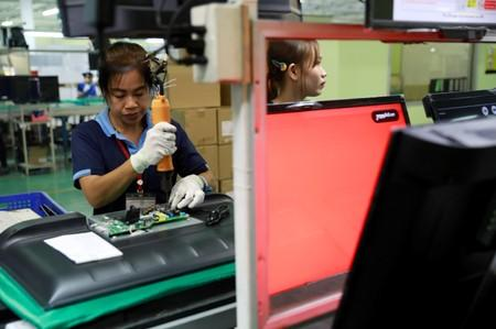 Migrant workers from Myanmar test the quality of monitors as they work on a TV assembly line at a factory in Bangkok