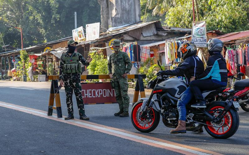 Soldiers direct traffic at a checkpoint in Tanay, Rizal, east of Manila - MARK R CRISTINO/EPA-EFE/Shutterstock