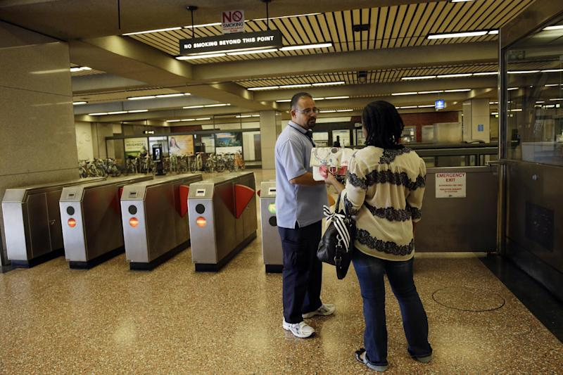 BART station agent Mark Madrigal helps a customer at the Lake Merritt station in Oakland, Calif., Friday, June 28, 2013. Two of San Francisco Bay Area Rapid Transit's largest unions gave notice that they plan to go on strike if they don't reach a new contract deal over the weekend. (AP Photo/Marcio Jose Sanchez)