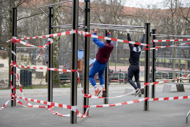 20 March 2020, Berlin: Two men training in the Volkspark Wilmersdorf at a fitness facility closed with a barrier tape, aimed at restricting the spread of coronavirus. Photo: Christoph Soeder/picture alliance via Getty Images
